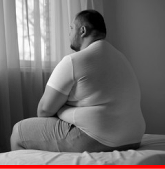 overweight man sitting on a bed